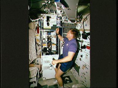 Crewmember in the middeck tending the CVTE and LBNP experiments.
