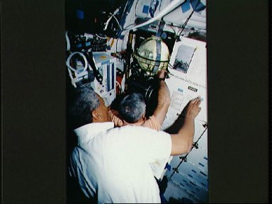 Crewmembers in the middeck with the FARE experiment.