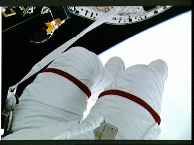 EVA crewmember's legs dangling over empty space and payload bay.