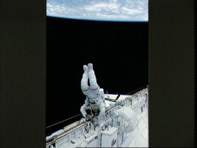 EVA Crewmember in the payload bay crawling along the starboard rail.