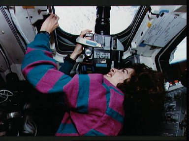 STS-56 MS3 Ochoa points HASSELBLAD 70mm camera out OV-103's overhead window