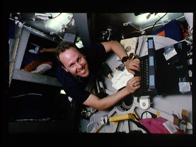 Astronaut Thomas Jones anchored to bunk facility while working on computer