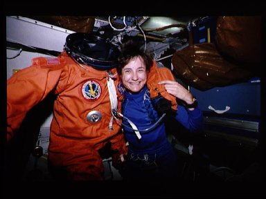 Astronaut Linda Godwin poses with spacesuit she wore for launch