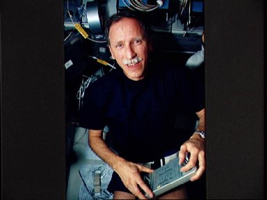 Astronaut Richard Covey with control box for bicycle ergometer