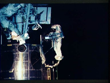 Astronaut Jeffrey Hoffman works with replacement WF/PC II for HST