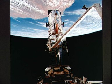 Astronauts Akers and Thornton remove one of HST solar arrays during EVA