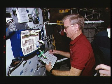 Astronaut John H. Casper checks equipment to support medical testing