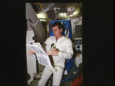 Astronaut Andrew M. Allen looks over procedure book in middeck
