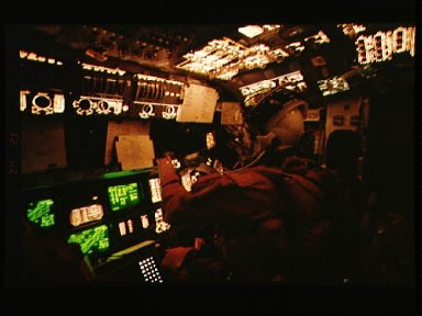 Astronaut Andrew M. Allen monitors Columbia's systems from pilots station