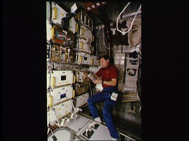 Russian cosmonaut Vladimir Titov works with samples for the CGBA