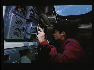 Astronaut Susan Helms on aft flight deck with RMS controls