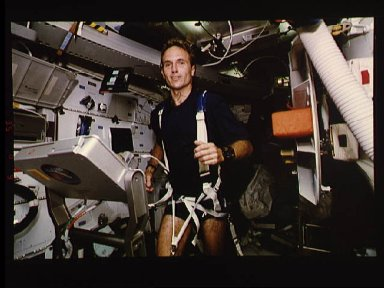 Astronaut Jerry Linenger works out on treadmill device on middeck