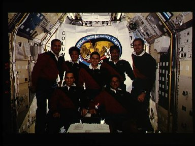 STS-65 crew onboard portrait in IML-2 spacelab module with mission flag