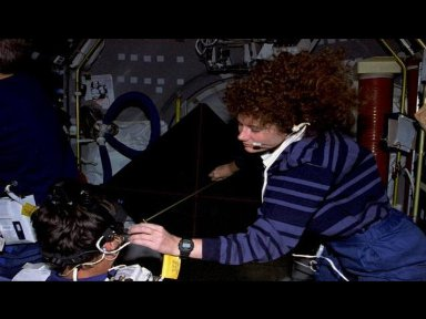 Astronaut Susan J. Helms, payload commander, measures the distance between Jean-Jacques Faviers head and the luminous torque, used for the Canal and Otolith Interaction Study (COIS) on the Life and Microgravity Spacelab (LMS-1) mission.