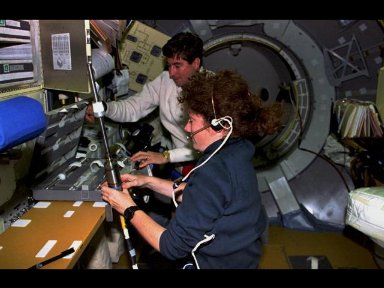 Astronauts Susan J. Helms, payload commander, and Terence T. (Tom) Henricks, mission commander, prepare a sample cartridge containing semiconductor crystals for Spacelab research.