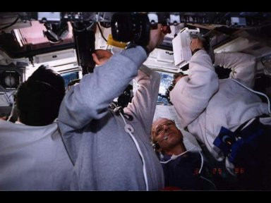 Astronaut Claude Nicollier is the only clearly identifiable crew member in this scene on the aft flight deck, captured during the busy chores associated with deployment of the Tethered Satellite System (TSS).