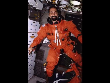 Payload specialist Umberto Guidioni, wearing the partial pressure launch and entry garment, prepares for the de-orbit phase of the 16-day flight.