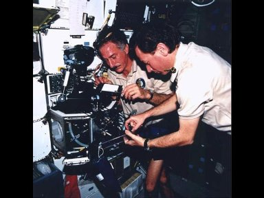 Astronauts Jeffrey A. Hoffman (left) and Maurizio Cheli, representing European Space Agency (ESA), set up an experiment at the glovebox on the Space Shuttle Columbias mid-deck.