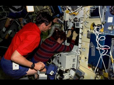 Astronaut Susan J. Helms, payload commander, and payload specialist Jean-Jacques Favier, representing the French Space Agency (CNES), insert a test container into the Bubble Drop Particle Unit (BDPU) in the Life and Microgravity Spacelab (LMS-1) Science M