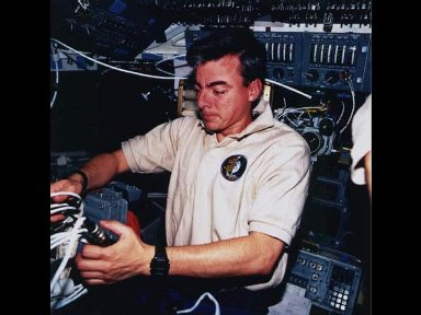 Astronaut Andrew M. Allen, mission commander, sets up systems for a television downlink on the flight deck of the Space Shuttle Columbia.