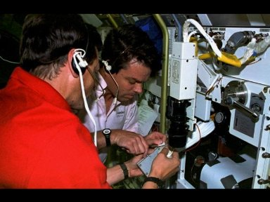 Payload specialist Jean-Jacques Favier, representing the French Space Agency (CNES), and astronaut Kevin R. Kregel, pilot, perform a successful Inflight Maintenance (IFM) on the Bubble Drop Particle Unit (BDPU).