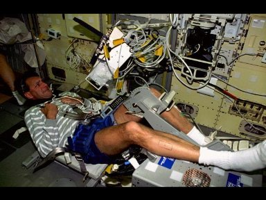 Astronaut Richard Linnehan, mission specialist, performs a test on his leg using the Torque Velocity Dynamometer (TVD).