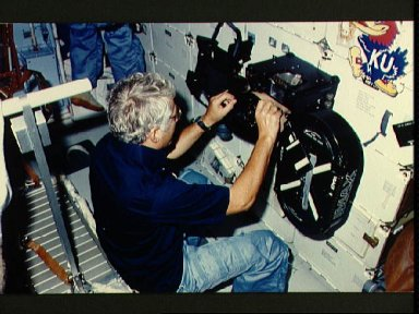 View of Crew Commander Henry Hartsfield Jr. loading film into IMAX camera