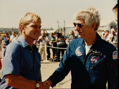 Crew commander Henry Hartsfield, Jr.is greeted by Astronaut George Nelson