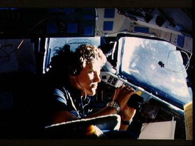 Astronaut Kathryn Sullivan using binoculars for magnifed viewing of earth