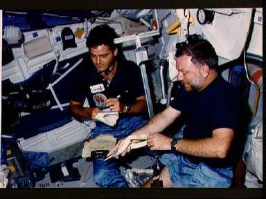 Payload specialists Garneau and Scully-Power prior to conducting experiments