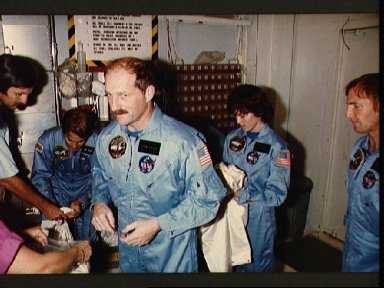 STS 51-A crew in lab coats for training with shuttle Discovery on launch pad