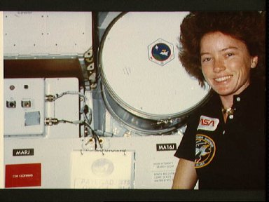 Astronaut Anna Fisher poses near a 3M experiment involving the DMOS