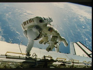 Astronaut Dale Gardner tethered to Discovery's starboard side.