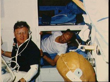 Astronaut Norman Thagard rests on middeck while other team is on duty