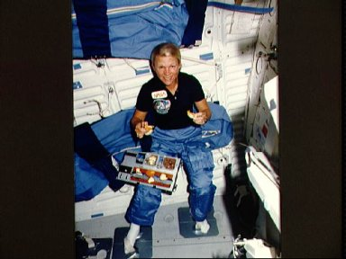 Astronaut Rhea Seddon sits down to a meal in the middeck