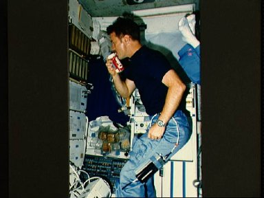 Astronaut Anthony W. England with soft drink in middeck area near galley
