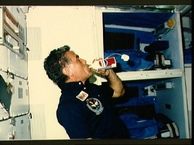 Astronaut Karl Henize with soft drink in middeck area