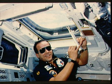 Payload specialist Patrick Baudry takes notes at the overhead flight window
