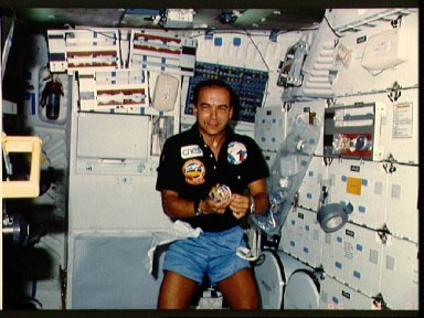 French payload specialist Patrick Baudry prepares a meal