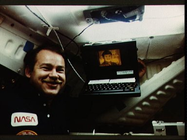 Astronaut John Creighton poses with onboard GRID computer