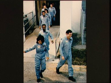 Crewmembers of the STS 51-L mission leave Operations and Checkout Building