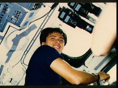Astronaut Franklin Chang-Diaz checking payload bay through aft deck window