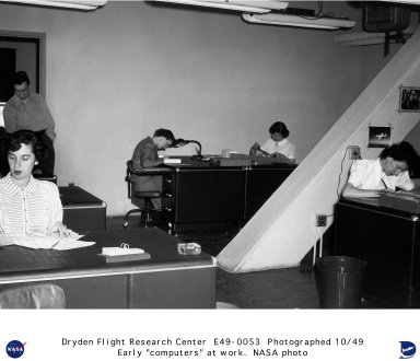 The women of the Computer Department at NACA High-Speed Flight Research Station are shown busy with test flight calculations. The computers under the direction of Roxanah Yancey were responsible for accurate calculations on the research test flights made at the Station. There were no mechanical computers at the station in 1949, but data was reduced by human computers. Shown in this photograph starting at the left are: Geraldine Mayer and Mary (Tut) Hedgepeth with Friden calculators on the their desks; Emily Stephens conferring with engineer John Mayer; Gertrude (Trudy) Valentine is working on an oscillograph recording reducing the data from a flight. Across the desk is Dorothy Clift Hughes using a slide rule to complete data calculations. Roxanah Yancey completes the picture as she fills out engineering requests for further data.