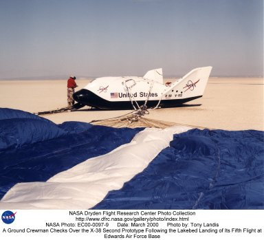 The X-38's blue and white parafoil spreads out in front of the research vehicle as it sits on a lakebed near the Dryden Flight Research Center after a March 2000 test flight.