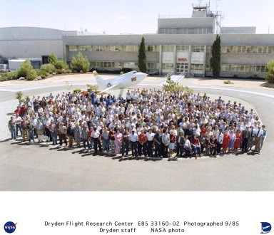 In 1985 the NASA Ames-Dryden Flight Research Facility employees and contractors gathered around the base of the X-1E for a picture. The X-1E is mounted in front of building 4800, the main building at Dryden. On Wednesday, October 1, 1958, the NACA yellow-backed winged symbol (see E-33718) that represented the National Advisory Committee for Aeronautics for 43-years, was removed from the front of the main building at the NASA High Speed Flight Station, making room for a new insignia belonging to the National Aeronautics and Space Administration. This NASA Insignia was created by retiree James J. Modarelli, former Chief of Technical Publication of Lewis Research Center; designed by the Army Institute of Heraldry; and approved by the Commission of Fine Arts and the NASA Administrator. This official insignia of the NASA is a dark blue disc with white stars. The white hand-cut letters ?NASA? are in the center of the disc and are encircled by a white diagonal orbit. A solid red ?V? shape appears behind and in front of the letters and extends beyond the disc. The ?V? is patterned after an actual wing design being tested by NACA researchers during the late 1950s. This insignia was used from 1958 to 1975 and was affectionately known at the ?meatball,? returning to NASA Insignia status in 1992. In the photo above the NASA Logotype appearing on the front of the main building replaced the NASA Insignia. The NASA Logotype was developed under the Federal Design Improvement Program initiated by the President in 1972, with the preferred color being red. It was approved by the Commission of Fine Arts and the NASA Administrator in October 1975. It symbolized NASA?s role in aeronautics and space from 1975 to 1992 and has since been retired. In the logotype, the letters ?NASA? are reduced with the strokes being of one width; the elimination of cross strokes in the two ?A? letters imparts a quality of uniqueness and contemporary character. This familiar logo was known as ?The Worm?. On 