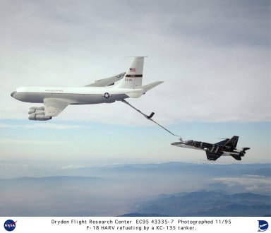 A thrust vectoring system can be seen mounted on the aft end of this NASA F-18 research aircraft at the Dryden Flight Research Center, Edwards, California, during an inflight refueling stop with a KC-135A (Serial #55-3135) tanker. The system was used to enhance its maneuverability and control at high angles of attack (high alpha) when conventional aerodynamic controls ? ailerons, rudders, and elevators ? are ineffective. The system features three spoon-shaped paddles mounted around the exhaust nozzles of each engine. The system, linked to the aircraft?s flight control system, moves the paddles into the exhaust flow to redirect thrust for directional control and increased maneuverability at angles of attack near 70 degrees. First research flights with the system operating began during the spring of 1991. Data from the F-18 High Alpha Research Vehicle (HARV) program produced information to validate computer codes and wind tunnel results and led to design methods providing better performance in future aircraft.