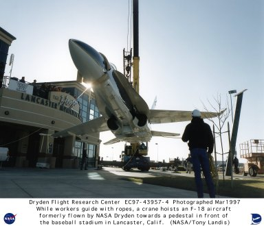 """Under the watchful eyes of news media and officials of the city of Lancaster, California, from a balcony, workers steady an F/A-18 Hornet airframe as it is gently lifted into the air prior to mounting on a pedestal in front of """"The Hangar,"""" the city's municipal stadium. The F/A-18 was formerly flown by NASA's Dryden Flight Research Center, Edwards, California, as a safety chase and support aircraft prior to its recent retirement. The aircraft is now mounted nose skyward on a 28-foot-tall pedestal on front of the stadium. The stadium is the home field of the Lancaster Jethawks, a Class-A farm team of the Seattle Mariners."""