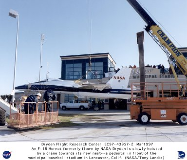 """An F/A-18 aircraft formerly flown by NASA's Dryden Flight Research Center, Edwards, California, is lifted by crane towards what has become its new home - a pedestal in front of the municipal baseball stadium in the city of Lancaster, California. The F/A-18 had been flown by NASA Dryden as a safety chase aircraft on research missions and for various other pilot proficiency and support duties prior to its recent retirement. The aircraft is now mounted nose skyward on the 28-foot-tall pedestal in front of the stadium, appropriately named """"The Hangar."""" The stadium is the home field of the Lancaster Jethawks, a Class-A farm team of the Seattle Mariners."""
