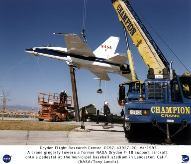 """A large crane gingerly lowers an F/A-18 Hornet aircraft onto a 28-foot-tall pedestal in front of the municipal baseball stadium in the city of Lancaster, California. The blue-and-white F/A-18 was recently loaned to the city by NASA's Dryden Flight Research Center, Edwards, California. NASA Dryden had flown the twin-jet aircraft as a safety chase and support aircraft over the past nine years. The stadium, known as """"The Hangar,"""" is the home field of the Lancaster Jethawks, a Class-A farm team of the Seattle Mariners."""