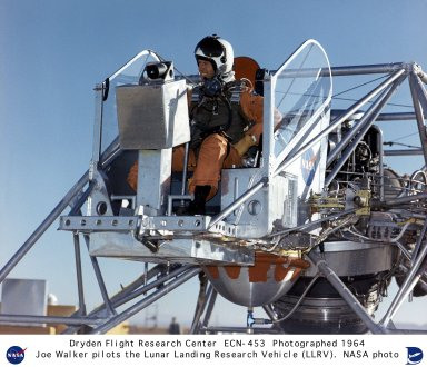 """In this 1964 NASA Flight Research Center photograph, NASA Pilot Joe Walker is setting in the pilot?s platform of the the Lunar Landing Research Vehicle (LLRV) number 1. This photograph provides a good view of the pilot setting in front of the primary instrumentation panel. When Apollo planning was underway in 1960, NASA was looking for a simulator to profile the descent to the moon's surface. Three concepts surfaced: an electronic simulator, a tethered device, and the ambitious Dryden contribution, a free-flying vehicle. All three became serious projects, but eventually the NASA Flight Research Center's (FRC) Landing Research Vehicle (LLRV) became the most significant one. Hubert M. Drake is credited with originating the idea, while Donald Bellman and Gene Matranga were senior engineers on the project, with Bellman, the project manager. Simultaneously, and independently, Bell Aerosystems Company, Buffalo, N.Y., a company with experience in vertical takeoff and landing (VTOL) aircraft, had conceived a similar free-flying simulator and proposed their concept to NASA headquarters. NASA Headquarters put FRC and Bell together to collaborate. The challenge was; to allow a pilot to make a vertical landing on Earth in a simulated moon environment, one sixth of the Earth's gravity and with totally transparent aerodynamic forces in a """"free flight"""" vehicle with no tether forces acting on it. Built of tubular aluminum like a giant four-legged bedstead, the vehicle was to simulate a lunar landing profile from around 1500 feet to the moon's surface. To do this, the LLRV had a General Electric CF-700-2V turbofan engine mounted vertically in gimbals, with 4200 pounds of thrust. The engine, using JP-4 fuel, got the vehicle up to the test altitude and was then throttled back to support five-sixths of the vehicle's weight, simulating the reduced gravity of the moon. Two hydrogen-peroxide lift rockets with thrust that could be varied from 100 to 500 pounds handled the LLRV's rate of de"""